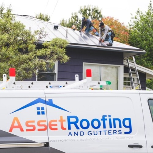Roofers Work on a Metal Roof.