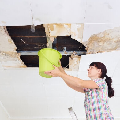 A Woman Puts Bucket Up to Ceiling Leak.