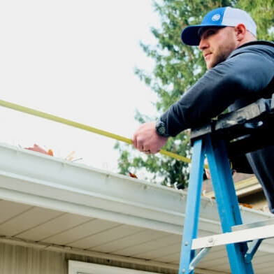 A Contractor Measures a Roof
